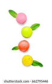 Colorful Macaroons with peppermint leaves on white background.