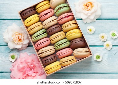 Colorful macaroons and rose flowers on wooden table. Sweet macarons in gift box. Top view