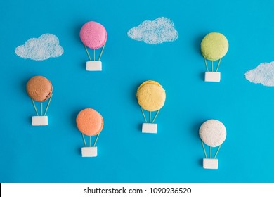 Colorful macaroons, sugar cubes and strings made of spaghetti with clouds in form of hot air balloons against blue sky background minimal creative concept.