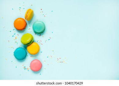 Colorful macaroons and sugar sprinkles arranged over blue background. Copy space.