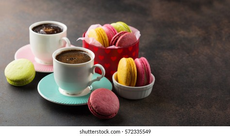 Colorful macaroons. Sweet macarons and cup of coffee on retro dark background with copy space. Selective focus. Holiday time concept