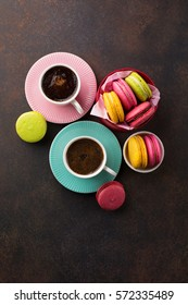 Colorful macaroons. Sweet macarons and cups of coffee on retro dark background with copy space. Top view. Holiday time concept