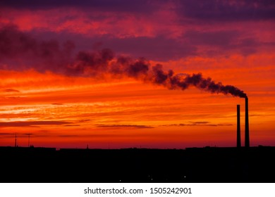 Colorful Magic Sunset. Roofs of city houses during sunrise. Dark smoke coming from the thermal power plant pipe.