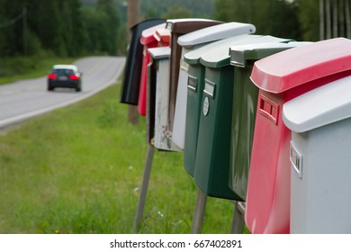 Colorful mailboxes near the road with car