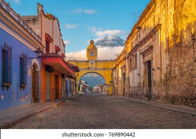 The colorful main street of Antigua City at sunrise with the famous yellow arch in the center and the active Agua volcano, Guatemala, Central America.
