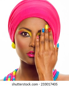 Colorful make up and manicure. African ethnic model with brown dark skin, headscarf and accessories. Beauty portrait, over white background, with copy space.
