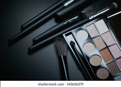 Colorful makeup palette and brush to apply powder. on pure black background.