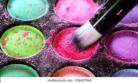 Colorful makeup palette with professional cosmetic brush.