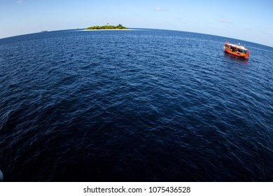 Colorful maldivian dhoni boat floating in wide open ocean with small island in background showing big round world