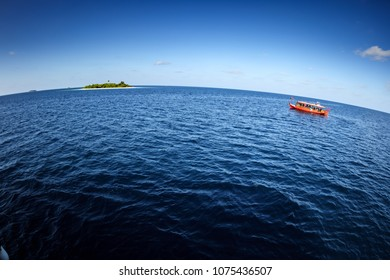 Colorful maldivian dhoni ferry boat approaches tropical island in open blue waters