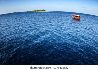 Colorful maldivian dhoni ferry boat floats in vast blue ocean near a tropical island