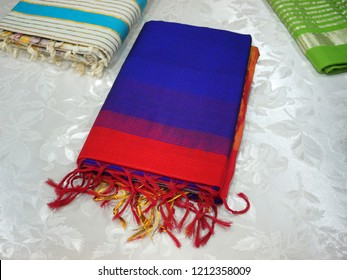 Colorful Managalagiri cotton sarees displayed for the customer in a textile shop, top-down composition.