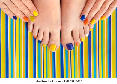 Colorful manicure on short nails and pedicure on striped background. Striped design.