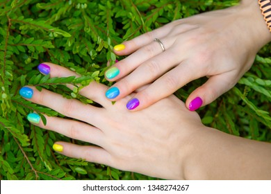 Colorful manicure on tropical background