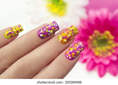 Colorful manicure with points on a lilac,yellow,pink,green background nails.