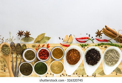 Colorful of many spices and herbs on white little bowl and spoons put on wood plank and isolated white background in top view flat lay with copy space. Food concept about homemade cooking and healthy.