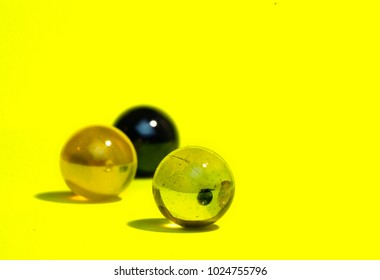 Colorful marbles on yellow background