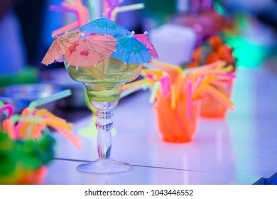 Colorful margarita cocktail isolated. Party time concept. Summer tropical cocktails. Barman´s table with straws, umbrellas and cocktails. Bokeh background.