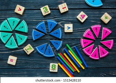 Colorful math fractions on wooden background or table. interesting math for kids. Education, back to school concept. Geometry and mathematics materials.