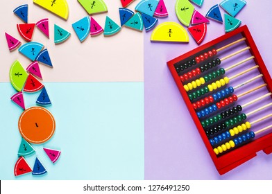 Colorful math fractions and wooden abacus on the pink blue violet bright backgrounds. Interesting math for kids. Education, back to school concept. Geometry and mathematics materials. Mental Math