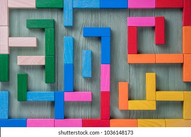 Colorful maze on brown background. The concept of a business strategy, analytics, search for solutions, the search output. Labyrinth of colorful wooden blocks, top view, flat lay.