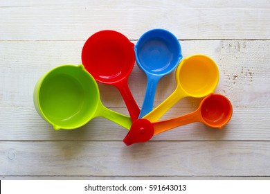 Colorful measuring spoons for kitchen on a white wooden background