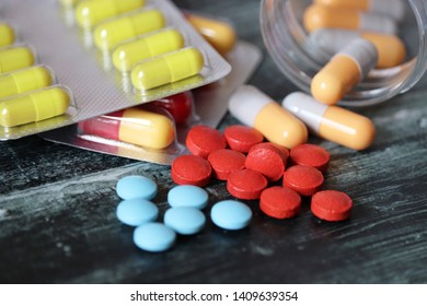 A lot of colorful medication, pills and capsules on dark wooden table close-up. Concept of pharmacy, vitamins, antibiotics, health care
