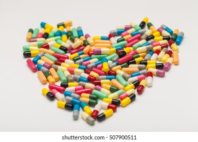 colorful of medicine on white background and heart shape.