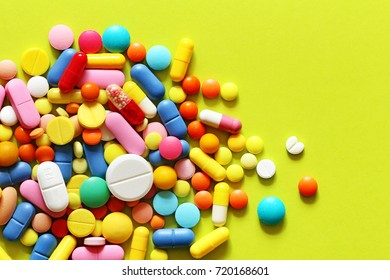 Colorful medicine pills on a green and yellow background