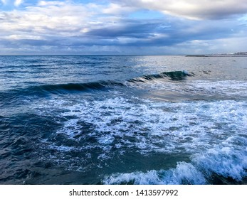 Colorful mediterranean sea in Marbella Europe. Clouds and small waves.