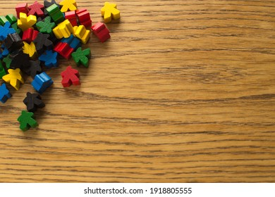 Colorful meeple on wooden background. Board game concept. Diversity of people and colors. The chips are out of order on the table.