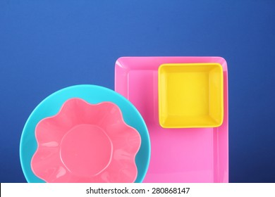 Colorful melamine utensils on blue background