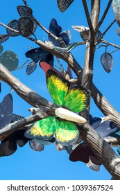 Colorful metal butterfly on the tree