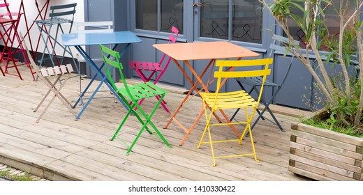 colorful metal chairs and table on empty terrace at cafe in web banner template
