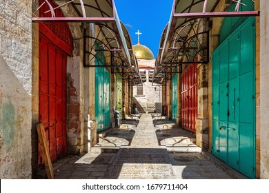 Colorful metal doors in a row as small church on background at famous market in old city of Jerusalem, Israel.