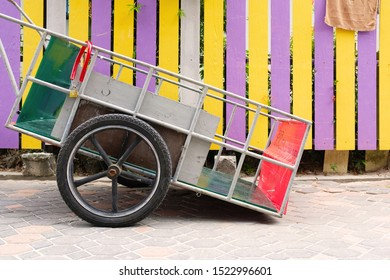 Colorful metal wheelbarrow / Pushcart and beautiful colorful fence detail / Street view