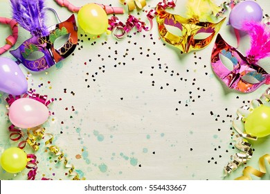 Colorful metallic foil carnival masks and party balloons forming a frame around central light green copy space with streamers and confetti