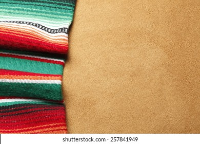 Colorful Mexican blanket on a brown suede surface