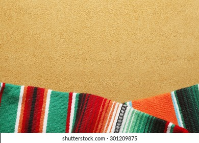 Colorful mexican blanket on warm gold background