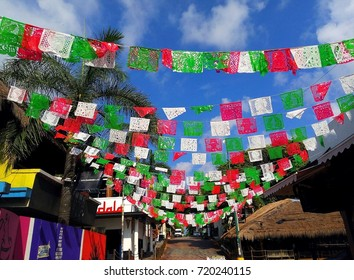 Colorful Mexican flags decorating street near Quinta Avenida (5th Avenue) in center of Playa del Carmen, Riviera Maya, Mexico for Mexican Independence Day / Cry of Dolores