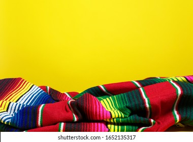 Colorful Mexican serape blanket on a yellow background
