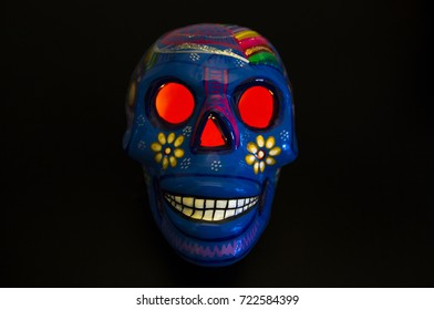 Colorful mexican skull with black background and candle lit inside. Dia de los muertos. Day of the Dead and Halloween.