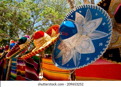 colorful Mexican sombreros and ponchos lined up outdoors