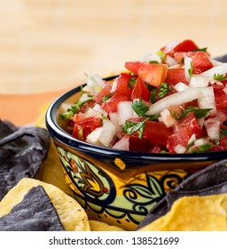 A colorful mexican style ceramic bowl filled with pico de gallo
