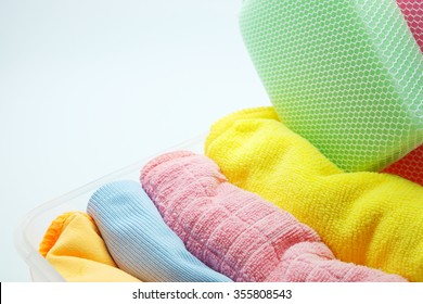 Colorful microfiber towel/cloth for car wipe with sponges in plastic box, gray background. Space for texts. Selective focus on pink and blue towels.