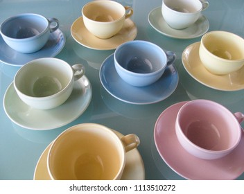 Colorful mid century modern coffee cups and saucers in pastel green, pink, blue and yellow have a retro look