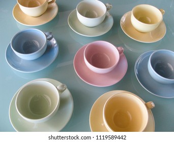 Colorful mid century modern coffee cups and saucers in pastel green, pink, blue and yellow have a retro look on a translucent glass table