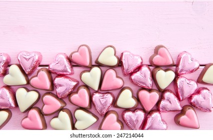 Colorful milk chocolates in heart-shapes on pink