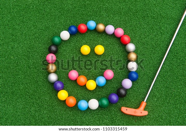 Colorful mini golf ball happy face with orange putter on synthetic grass