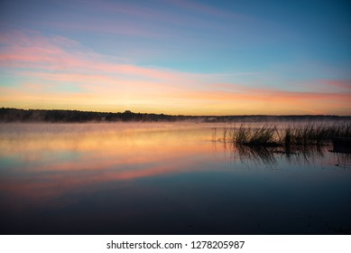 colorful misty sunset on the river in summer with dark trees in background. colored sky and dramatic red colors on calm water